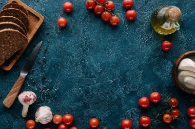 Ripe red tomatoes with bread and spices on dark blue table
