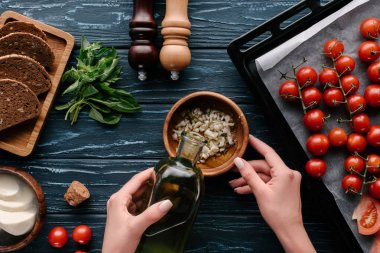 Cropped view of female hands adding oil to garlic on dark wooden table with tomatoes and herbs