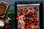 Woman pouring garlic sauce on tomatoes on baking pan by cooking ingredients