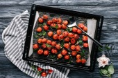 Fotografie Baking pan with red cherry tomatoes on dark wooden table