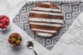 felülnézet finom barna torta cukor por és a friss bogyós gyümölcsök a márvány felületre