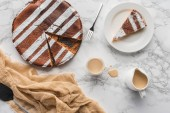 Photo top view of tasty homemade cake with sugar powder and hot chocolate on marble surface
