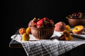 Fotografie Selektivní fokus mísa s jahody, broskve a meruňky na dřevěný stůl na černém pozadí