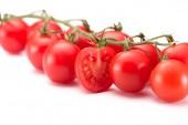 zblízka pohled zralé cherry rajčat na větvičku izolované na bílém