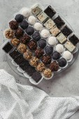 Fotografie pohled shora uspořádány různé sladké dezerty na desce a ubrus na šedém povrchu