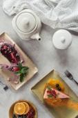 plochý ležela s sladký mrkvový dort s berry plnění, borůvkový koláč podávaný s mátové lístky a okvětními, konvice a ložní prádlo na šedou desku