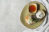 pohled shora samosas filo těsta plněný špenátem a paneer zdobené klíčící semena vojtěšky a slunečnice, podávané na talíř na šedém povrchu