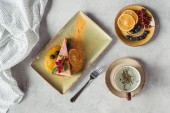 Fotografia flat lay with piece of sweet carrot cake with berry filling served with orange slice, cup of herbal tea, and fork on grey tabletop