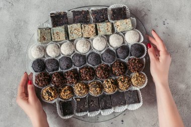 partial view of woman holding plate with various sweet desserts on grey tabletop