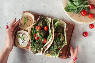 cropped shot of woman holding falafel with tortillas, cherry tomatoes and germinated seeds of sunflower served on wooden board on grey surface