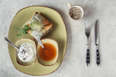Flat lay with samosas in phyllo dough stuffed with spinach and paneer decorated with germinated seeds of alfalfa and sunflower served on plate on grey tabletop stock vector