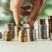 cropped view of person stacking coins on table on blurred green background