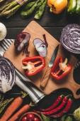 pohled shora na prkénku s nožem a různé čerstvé zeleniny na dřevěnou desku