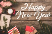 top view of frame of christmas gifts on rustic wooden table, happy new year inscription