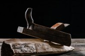 Fotografie  close up view of vintage woodworker plane and stump isolated on black