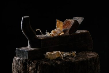 close up view of vintage woodworker plane on wooden stump isolated on black