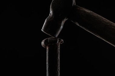 Close up view of vintage hammer and nail isolated on black stock vector
