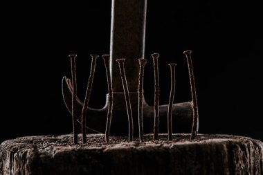 close up view of vintage rusty hammer and nails on wooden stump isolated on black