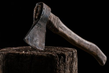 close up view of vintage axe on wooden stump isolated on black