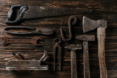 flat lay with assortment of vintage rusty carpentry tools on wooden surface