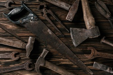 flat lay with assortment of vintage rusty tools on wooden surface