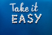 Fotografie top view of lettering take it easy made by white pills on blue background