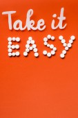 Fotografie top view of lettering take it easy made by white pills on red background