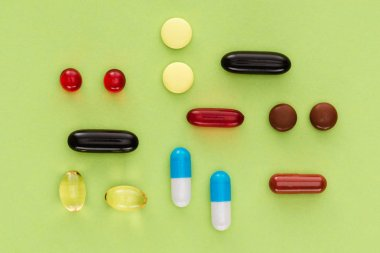 top view of arranged various pills on green background