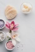 schöne Orchideenblüten, Meersalz in Schalen und Schwämmen auf weißem Hintergrund
