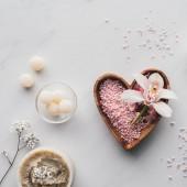 pohled shora bílý květ orchideje a růžové mořské soli v misce ve tvaru srdce na bílém