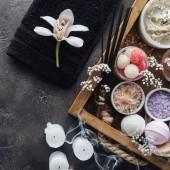 pohled shora krásnou orchidej, ručník, svíčky a příslušenství pro péči o tělo na grey