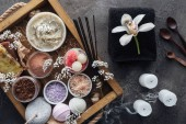 Fotografie top view of orchid flower, towel, candles and spa accessories in wooden box on grey