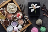Fotografie top view of orchid flower, towel and spa accessories in wooden box on grey