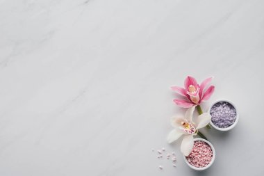 top view of beautiful orchid flowers and sea salt in bowls on white background