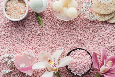 top view of beautiful orchid flowers, handmade soap, sponges and pink sea salt