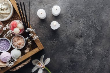 top view of spa and bath accessories in wooden box and burning candles on grey background