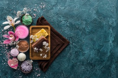 top view of handmade soaps, flowers, sea salt and towels on dark background