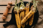 Fotografie top view of grilled corn, salt grinder on wooden table with sackcloth