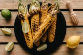 Fotografie top view of grilled corn on plate surrounded by lime slices and lemon with squeezer on wooden table