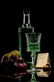 Fotografie Nahaufnahme der Absinth mit Reifen Früchten und Käse auf Spiegelfläche auf schwarz