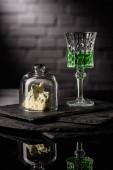 Fotografie Nahaufnahme der Glas Absinth mit Scheibe Käse auf dunklen Ziegel Wand Hintergrund
