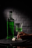 Photo cropped shot of woman holding glass of absinthe on dark brick wall background