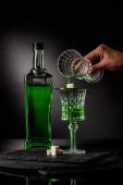 Fotografie Schuss von Frau Gießen Absinth im Glas und auf Zuckerwürfel auf dunklem Hintergrund abgeschnitten