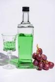 Fotografie Kristallglas und Flasche Absinth mit Zweig der Trauben auf weiß