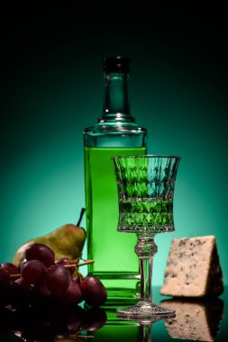 close-up shot of absinthe with fruits and cheese on mirror surface on dark blue background