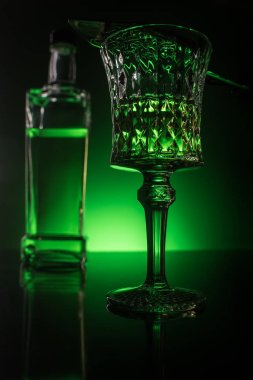close-up shot of glass with absinthe and bottle on reflective surface and dark green background