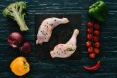 Photo top view of chicken legs on stone slate with different vegetables on dark green wooden tabletop