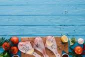 Ansicht von Hühnerkeulen auf Holzbrett mit verschiedenen Gemüsesorten auf blauer Tischplatte