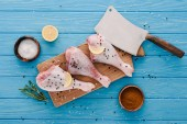 pohled shora syrové kuřecí stehýnka na dřevěné desce s kořením a sekáček na modrou desku