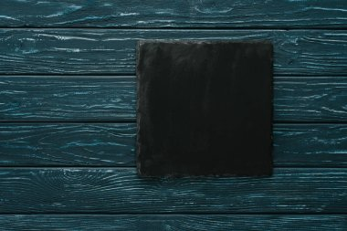 top view of black stone cutting board on green wooden tabletop